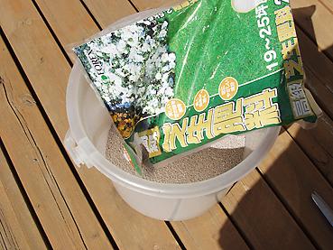 芝生の肥料をバケツに入れる