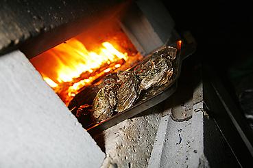 石窯で牡蠣を焼く