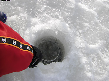 ワカサギ釣りの穴の氷を取り除く